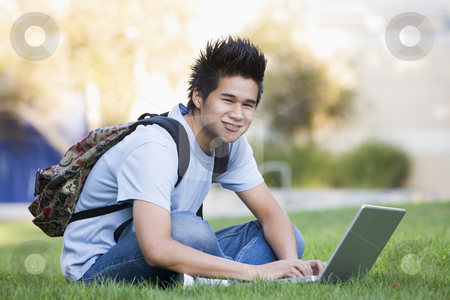 University student with laptop computer stock photo, Male student sitting on grass with laptop by Monkey Business Images