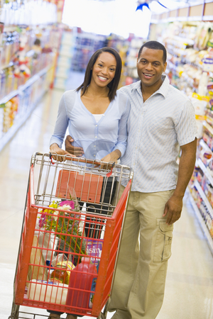 Couple grocery shopping stock photo, Young couple grocery shopping in supermarket by Monkey Business Images