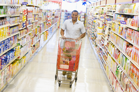 Young man grocery shopping stock photo, Young man grocery shopping in supermarket by Monkey Business Images