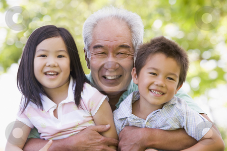 Grandfather posing with grandchildren stock photo,  by Monkey Business Images