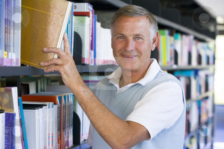 Senior man pulling a library book off shelf stock photo,  by Monkey Business Images
