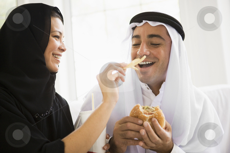 A Middle Eastern couple sharing a fast food meal stock photo,  by Monkey Business Images