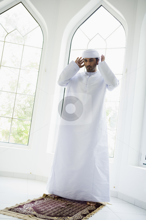 A Middle Eastern man praying stock photo,  by Monkey Business Images