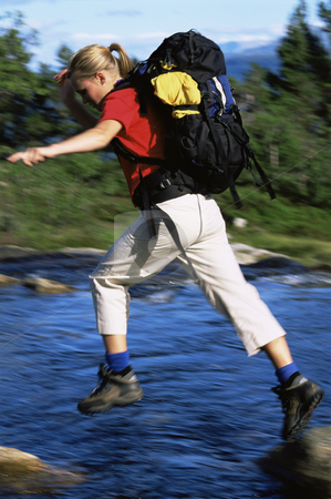 Hiker jumping from rock to rock while crossing river stock photo,  by Monkey Business Images
