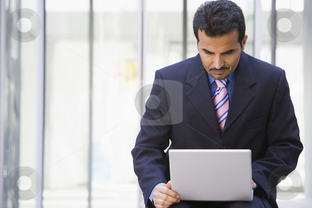 Businessman using laptop outside office stock photo, Businessman using laptop outside office by Monkey Business Images
