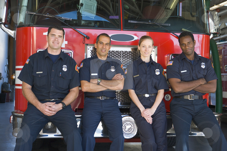 Portrait of firefighters standing by a fire engine stock photo,  by Monkey Business Images