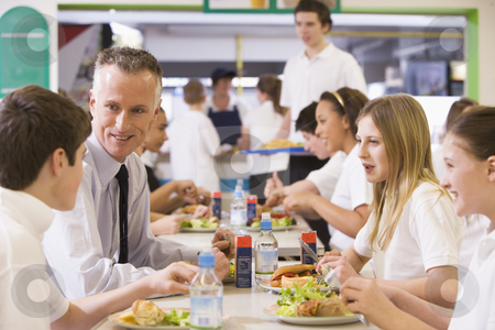 A teacher eating lunch with his students in the school cafeteria stock photo,  by Monkey Business Images