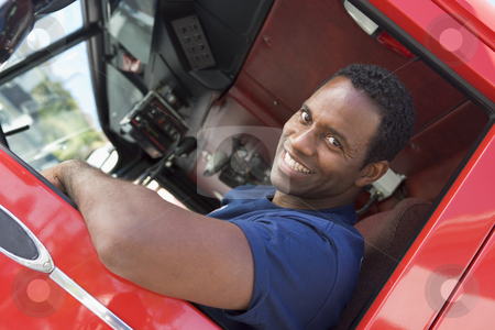 A firefighter sitting in the cab of a fire engine stock photo,  by Monkey Business Images