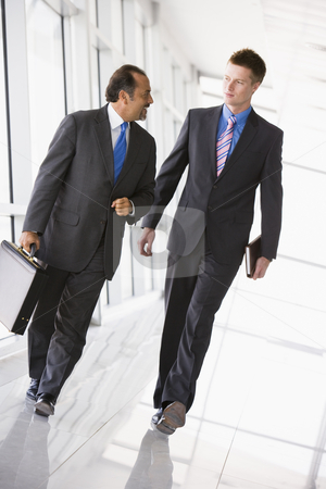 Businessmen walking through lobby stock photo, Businessmen walking through office lobby by Monkey Business Images