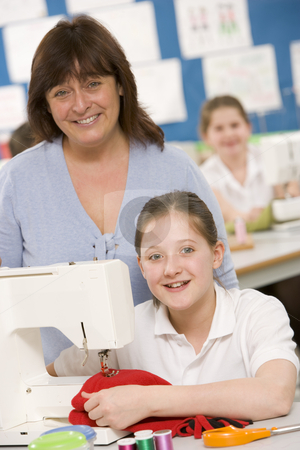 Teacher and schoolgirl using a sewing machine in sewing class stock photo,  by Monkey Business Images