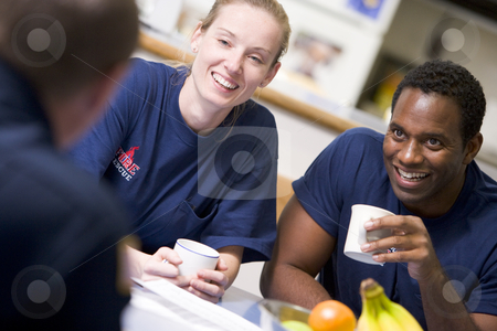Firefighters relaxing in the staff kitchen stock photo,  by Monkey Business Images