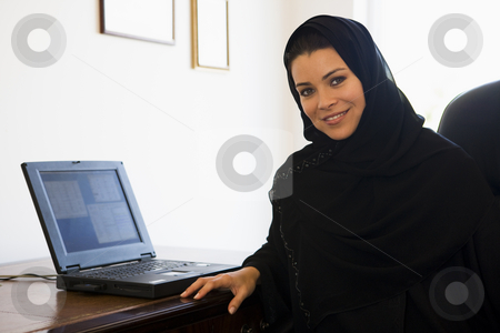 A Middle Eastern woman sitting in front of a computer at home stock photo,  by Monkey Business Images