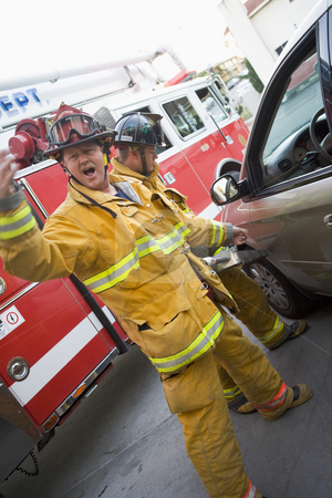 Firefighters cutting open a car to help an injured person stock photo,  by Monkey Business Images