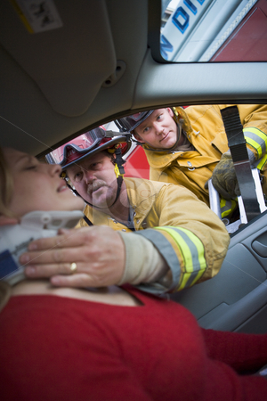 Firefighters helping an injured woman in a car stock photo,  by Monkey Business Images