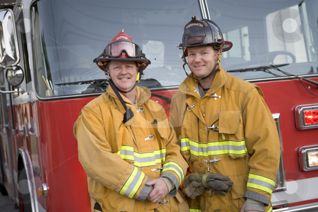 Portrait of two firefighters by a fire engine stock photo,  by Monkey Business Images
