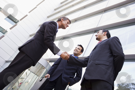 Group of businessmen shaking hands outside office stock photo, Group of businessmen shaking hands outside modern office by Monkey Business Images