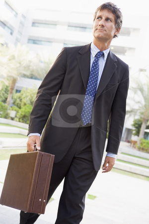 Businessman walking outdoors stock photo,  by Monkey Business Images