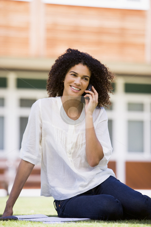 A woman on her mobile phone sitting on a campus lawn stock photo,  by Monkey Business Images