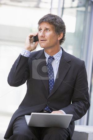 Businessman sitting in office lobby with laptop using cellular p stock photo,  by Monkey Business Images