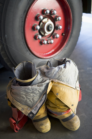 Empty firefighter's boots and uniform next to fire engine stock photo,  by Monkey Business Images