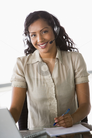Female telesales worker stock photo, Female telesales worker in office by Monkey Business Images