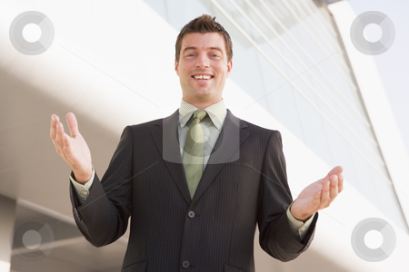 Businessman standing outdoors by building with hands out stock photo,  by Monkey Business Images