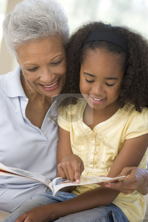Grandmother and granddaughter reading and smiling stock photo,  by Monkey Business Images