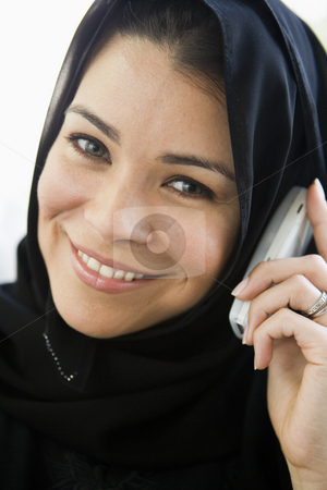 A middle eastern woman talking on a cellphone stock photo,  by Monkey Business Images