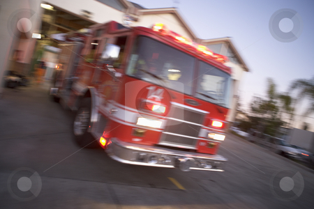 Fire engine rushing out of a fire station stock photo,  by Monkey Business Images