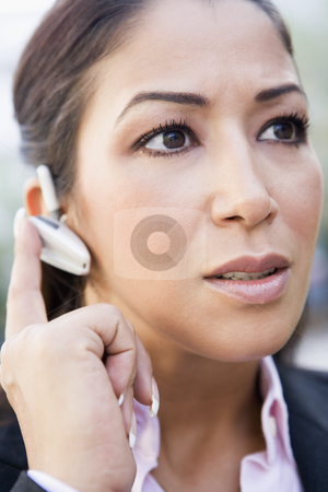 Woman using bluetooth earpiece  stock photo, Woman using bluetooth earpiece outside by Monkey Business Images