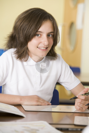 A schoolgirl studying in class stock photo,  by Monkey Business Images