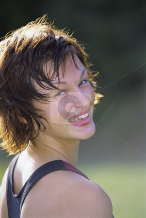 Sportswoman looking over shoulder and smiling at camera stock photo,  by Monkey Business Images