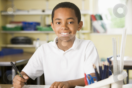 A schoolboy studying in class stock photo,  by Monkey Business Images