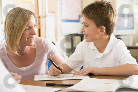 A schoolboy sitting with his teacher in class stock photo,  by Monkey Business Images