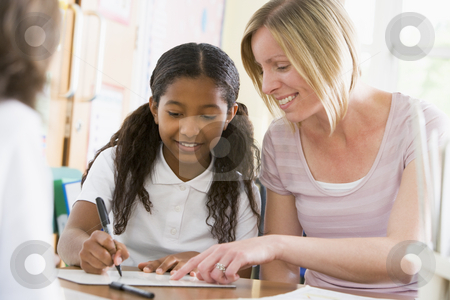 A schoolgirl sitting with her teacher in class stock photo,  by Monkey Business Images