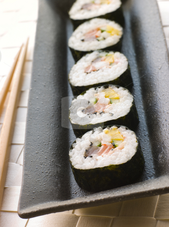 Large Spiral Rolled Sushi stock photo, Plate of Large Spiral Rolled Sushi with chopsticks by Monkey Business Images
