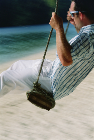 Man on swing at beach stock photo,  by Monkey Business Images