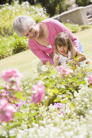 Grandmother and granddaughter outdoors in garden smiling stock photo,  by Monkey Business Images
