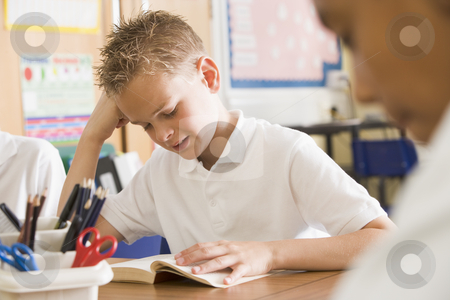 Schoolboy reading a book in class stock photo,  by Monkey Business Images