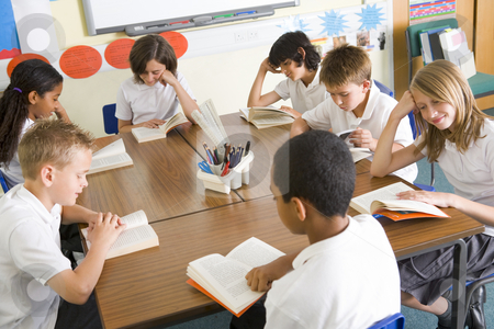 Schoolchildren reading books in class stock photo,  by Monkey Business Images