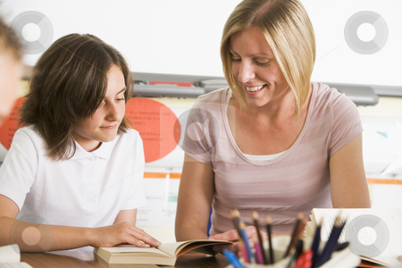 A schoolgirl and her teacher reading a book in class stock photo,  by Monkey Business Images