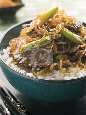 Sweet Soy Beef Fillet with Shirataki Noodles on Rice stock photo, Bowl of Sweet Soy Beef Fillet with Shirataki Noodles on Rice with chopsticks by Monkey Business Images
