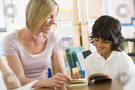 A schoolboy and his teacher reading a book in class stock photo,  by Monkey Business Images