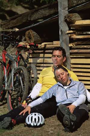 Exhuasted couple resting beside mountain bikes stock photo,  by Monkey Business Images