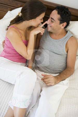 A Middle Eastern couple lying on a bed stock photo,  by Monkey Business Images