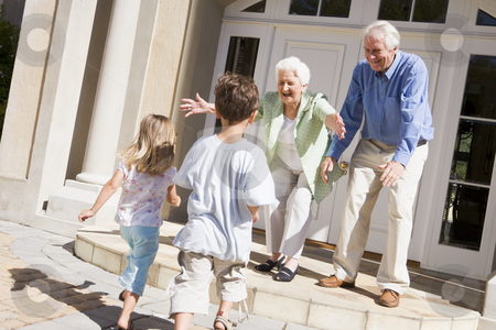 Grandparents welcoming grandchildren stock photo,  by Monkey Business Images