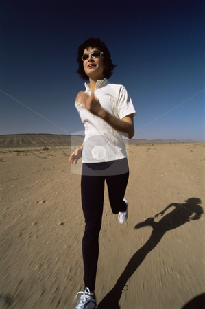Young woman jogging in desert stock photo,  by Monkey Business Images