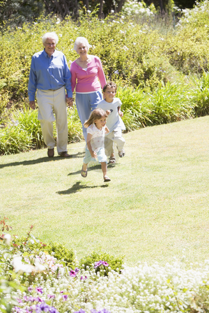 Grandparents walking with grandchildren stock photo,  by Monkey Business Images