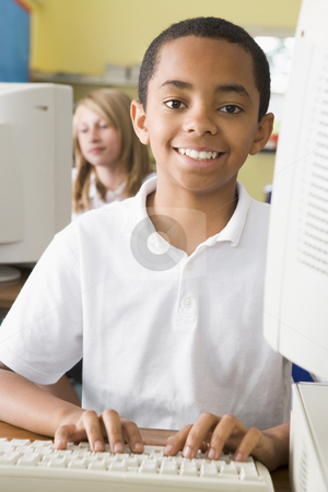 Schoolboy studying in front of a school computer stock photo,  by Monkey Business Images