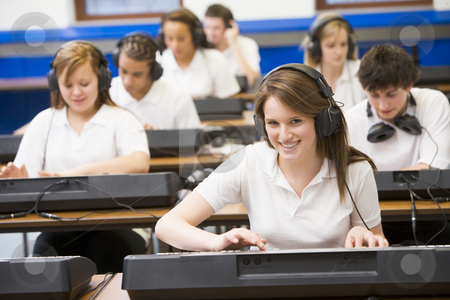 Schoolchildren practicing on a keyboard in music class stock photo,  by Monkey Business Images